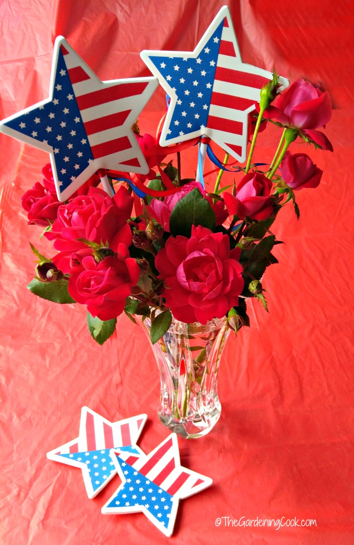 Patriotic Rose Vase decor with star flags on a red tablecloth.