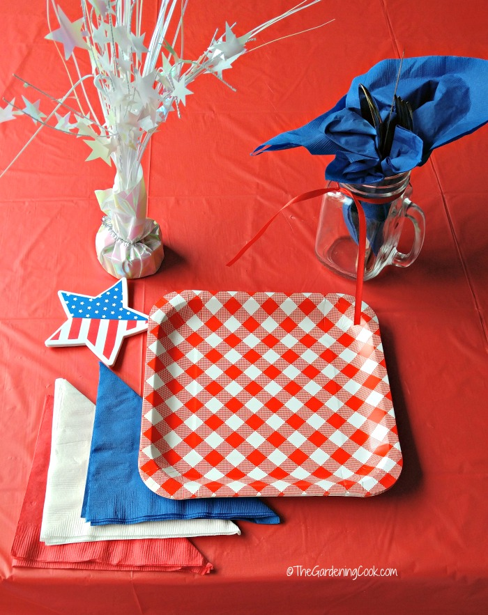 Patriotic table setting with star paperweiught, blue napking in mason jar, red white and blue napkins, flag star and red and white plates.