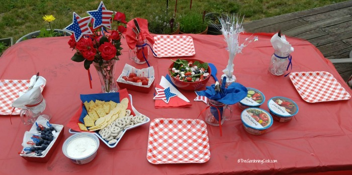 Patriotic Tablescape for the fourth of July on a red table outdoors.