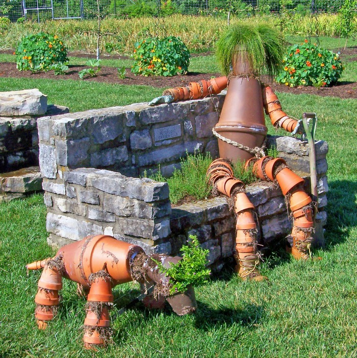 Arrange terracotta pots in the shame of a seated man and dog for a wonderful display of garden art