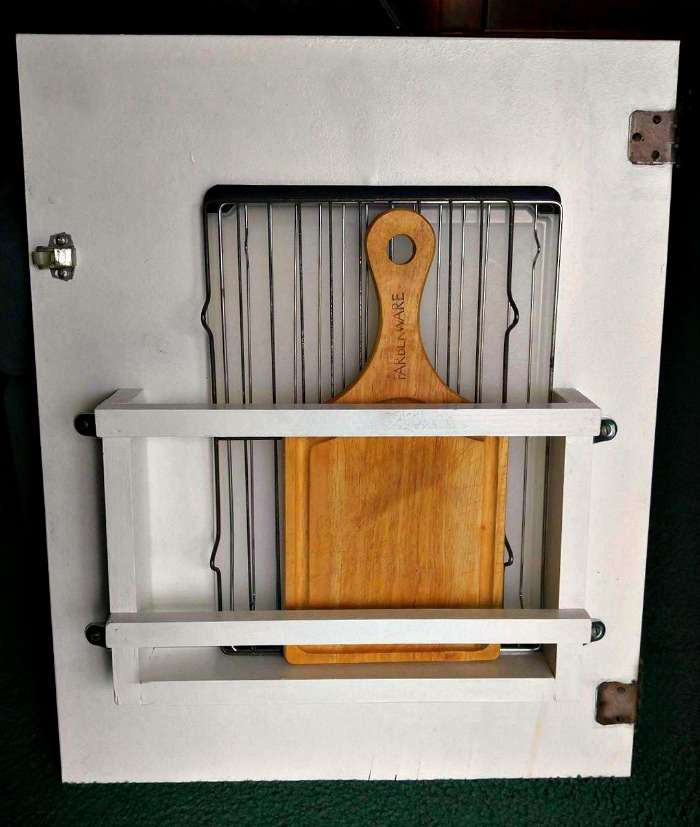 The cutting board holder is attached to the cabinet door