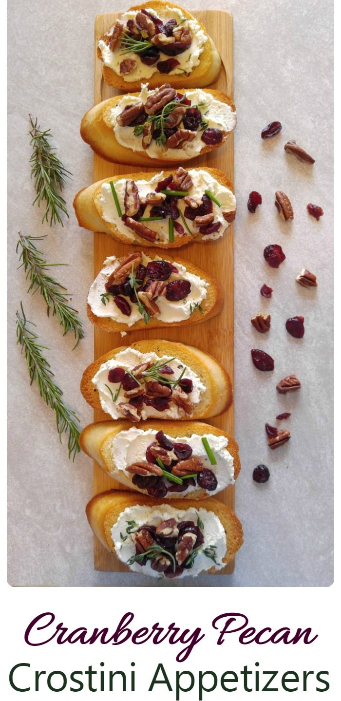 Crostini slices with cranberries and nuts over cheese spread and words reading cranberry pecan crostini appetizers.