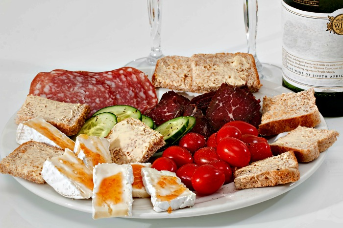 White antipasti platter with sliced meats and vegetables.
