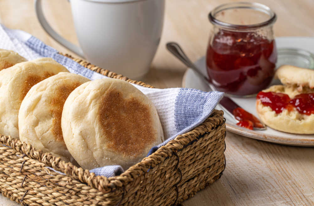 English muffins in a basket with some jam.