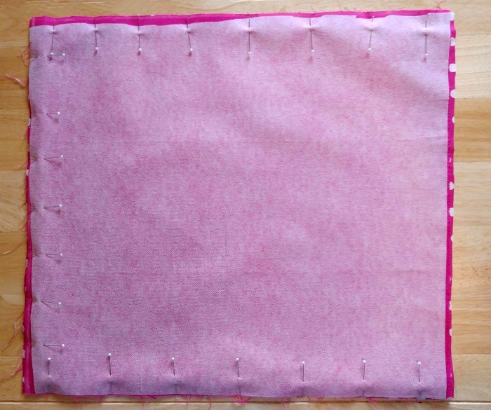 Fusing on one piece of pink fabric pinned in place.
