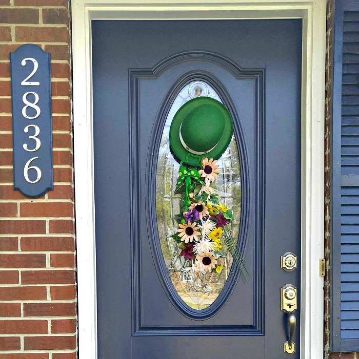 St. Patrick's Day Door wreath on a blue door with a leprechaun hat.