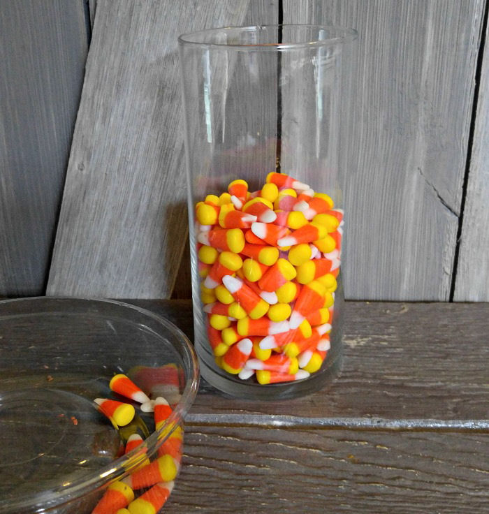 Add candy corn to a glass vase