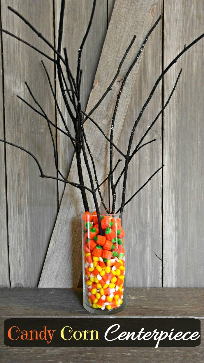 Candy corn and black tree branches makes a great table centerpiece for Halloween
