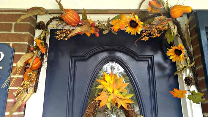 An autumn wreath is draped over the door