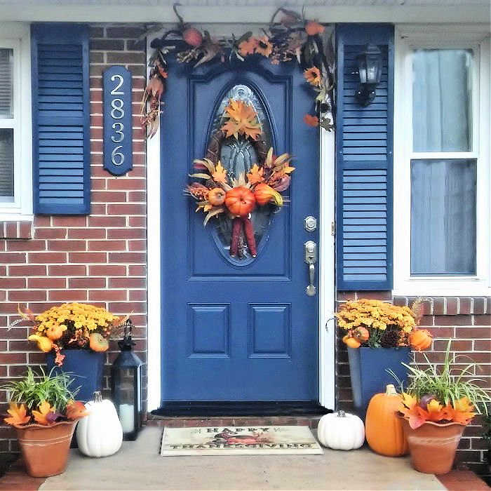 Blue door with greenery for fall and planters in an entryway..