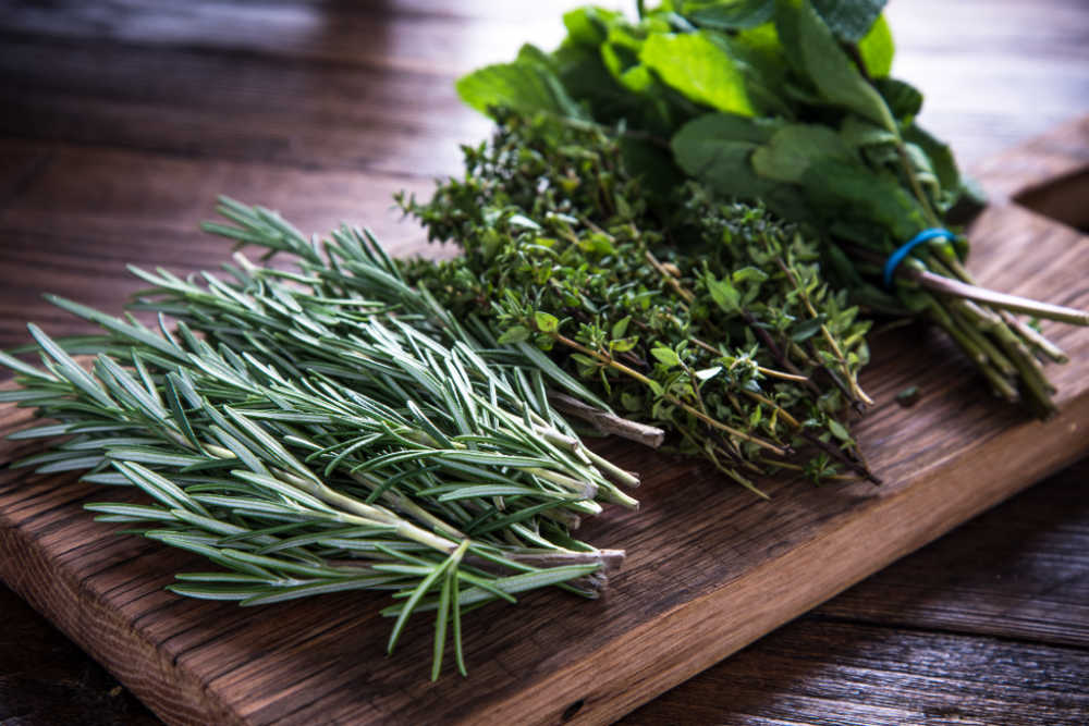 Bunches of fresh herbs on a cutting board.