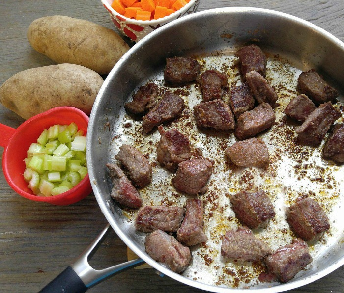 Browned beef in a saute pan and vegetables