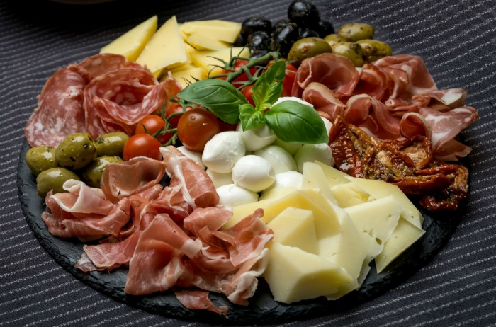 Antipasti platter loaded with meat and cheese.