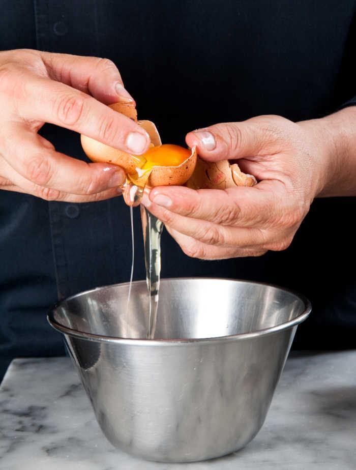 Man in a black shirt separating egg yolks from egg whites.