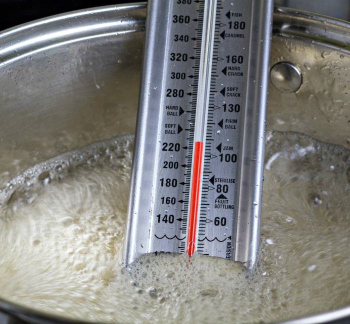 candy thermometer in a pot of sugar.