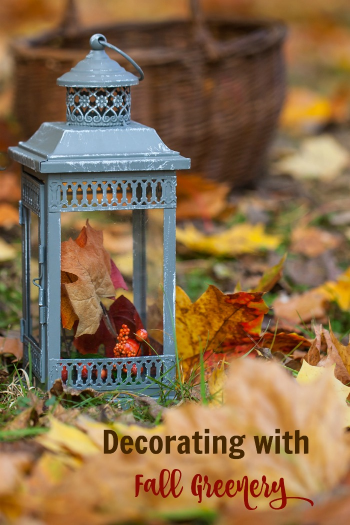 "Lantern and leaves with text reading ""Decorating with fall greenery."""