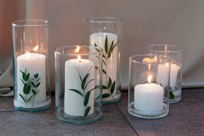 White candles with eucalyptus leaves on holders.