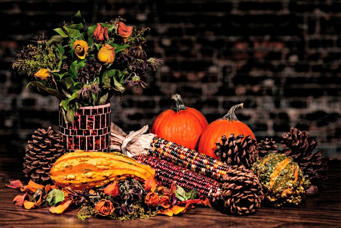 Indian corn and other fall greenery items on a table.