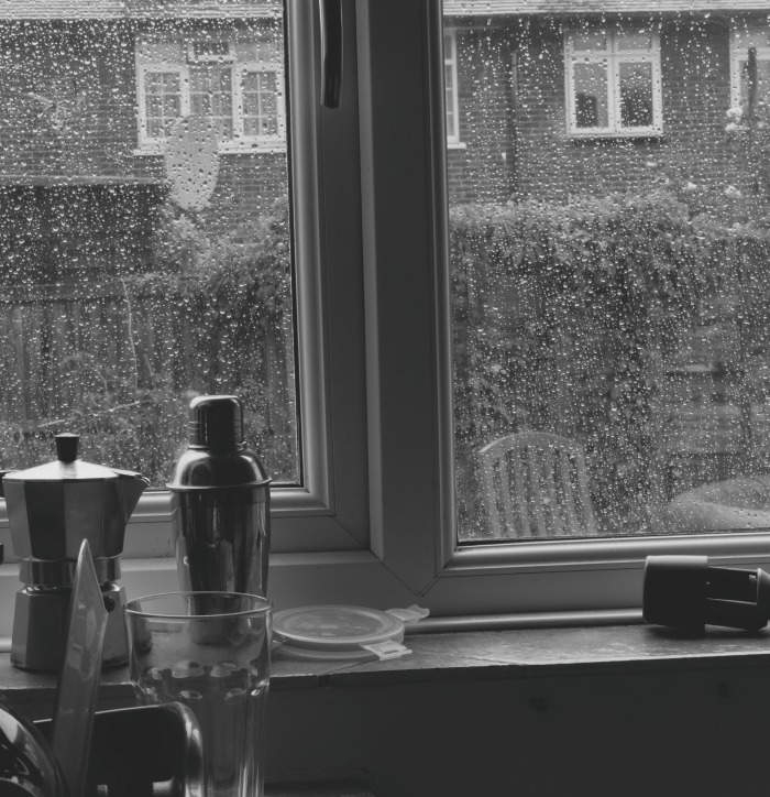 A kitchen window with rain outside.