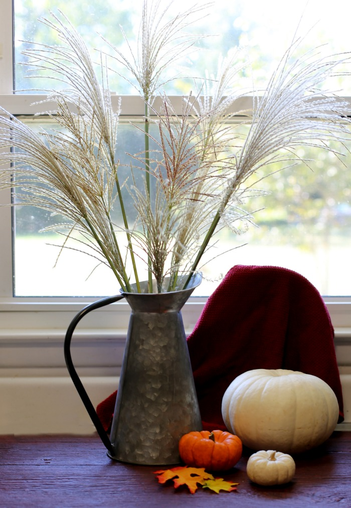 Decorating with natural elements: Silver Grass fronds in a galvanized pitcher with pumpkins