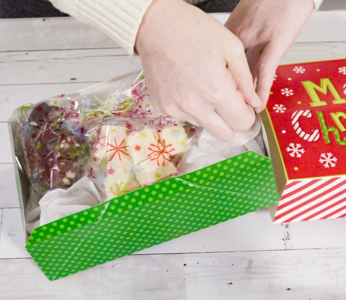Wrapping fudge in plastic in a Christmas gift box.