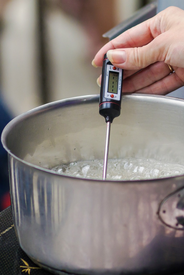 Female hand testing a candy thermometer.