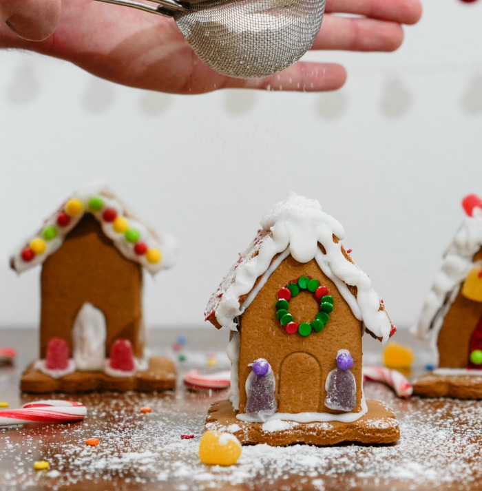 Dusting a gingerbread house with a sifter and sugar.