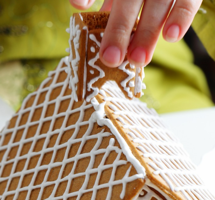 Adding a gingerbread chimney to the roof of the house.