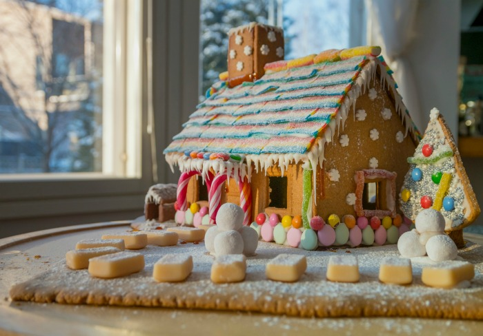 Gingerbread house decorated with candy near a sunny window.