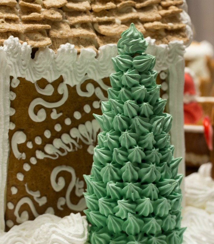 Waffle cone Christmas trees with green frosting near a gingerbread house.