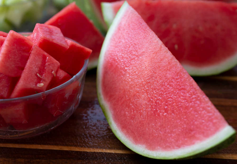 Half a seedless watermelon and bowl of cut slices.