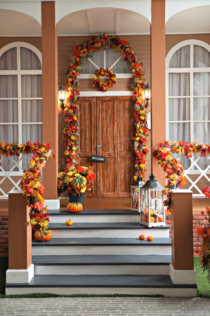 Pumpkins and leaves on a fall porch.