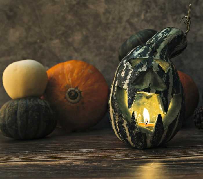 carved gourd with a candle inside and pumpkins.
