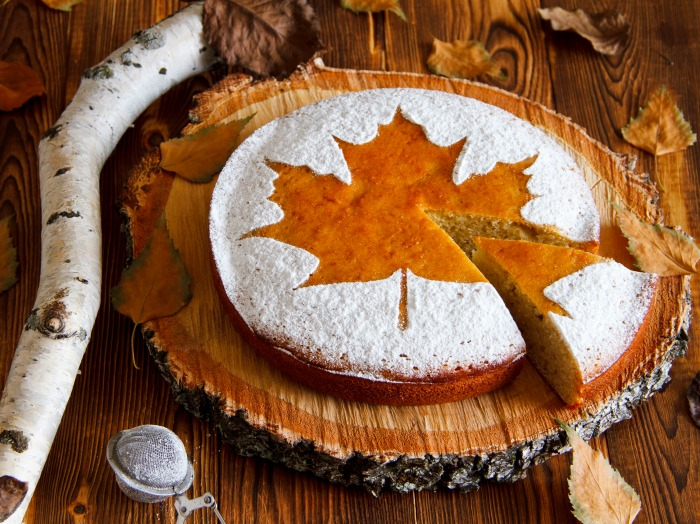 Cake with a maple leaf design and powdered sugar round it.