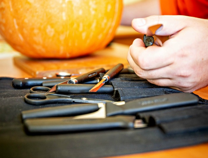 Set of pumpkin carving tools, mans hand and pumpkin.