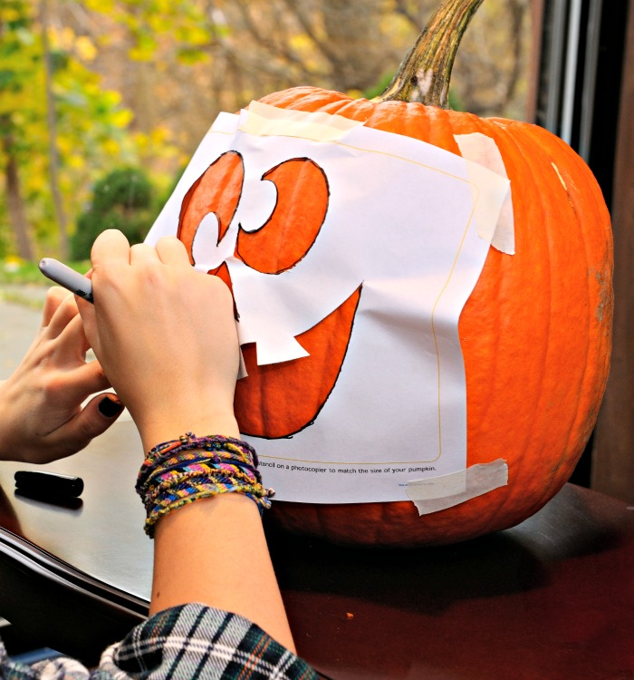 Using a pumpkin carving stencil.