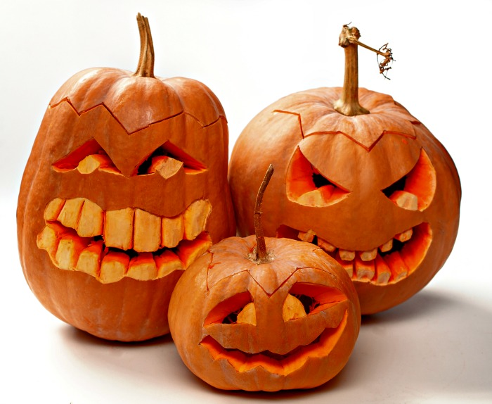Trio of grinning carved pumpkins with big teeth.