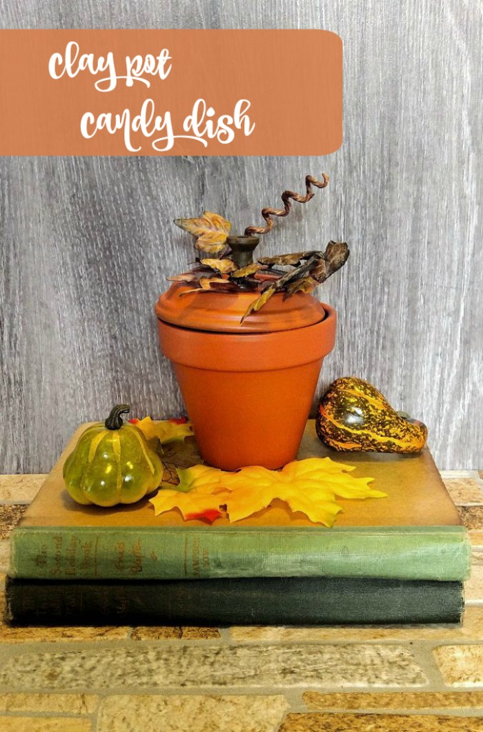 Terra cotta pumpkin Candy dish made of a clay pot on a stack of vintage books
