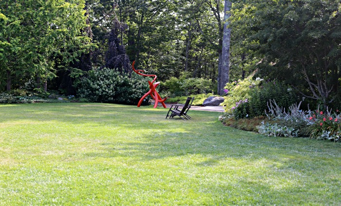 Cleaver lawn with statue and Adirondack chair in Coastal Maine Botanical Garden