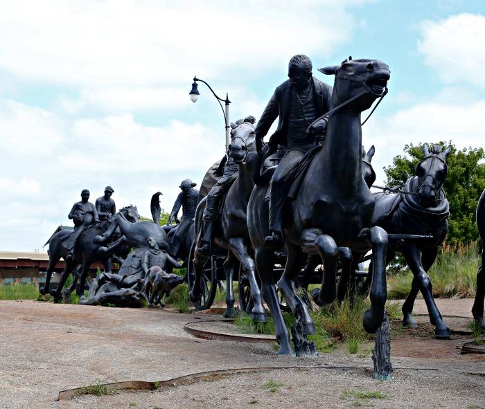 Wagon train made of bronze statues