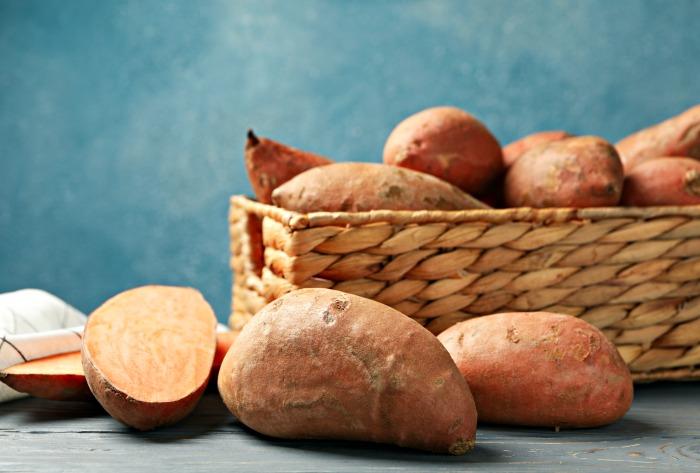 A basket of healthy sweet potatoes and a cut sweet potato.