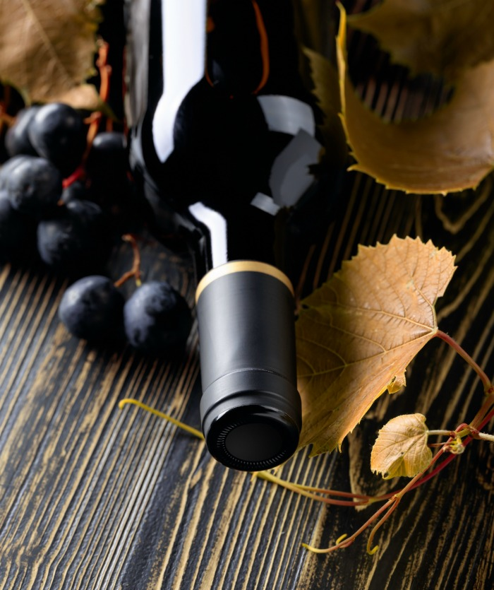 Bottle of Merlot wine with grapes and leaves.