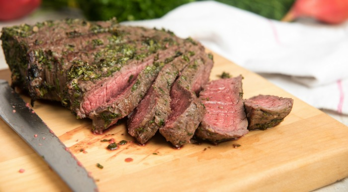 Grilled London Broil on a cutting board with a knife.