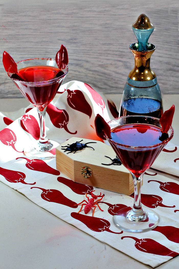 Halloween cocktail garnishes - devil horns garnish on a red drink with chili pepper towel and decanter.