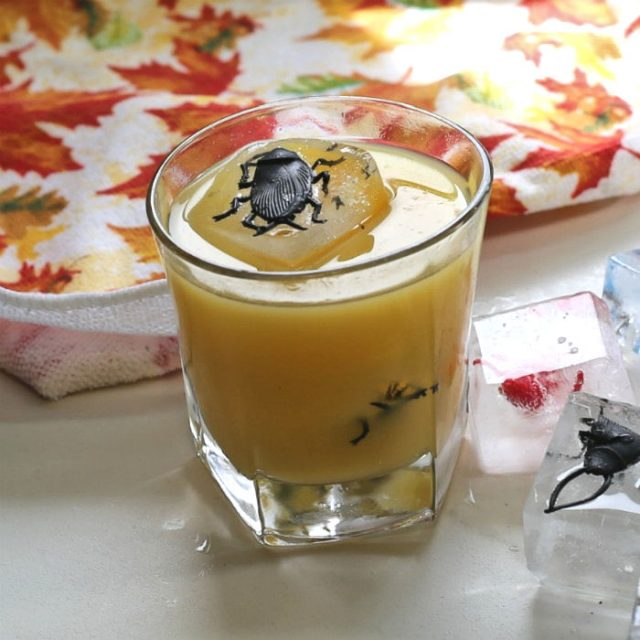 Halloween cocktail special effects - spider ice cubes in orange drink with leaf towel.
