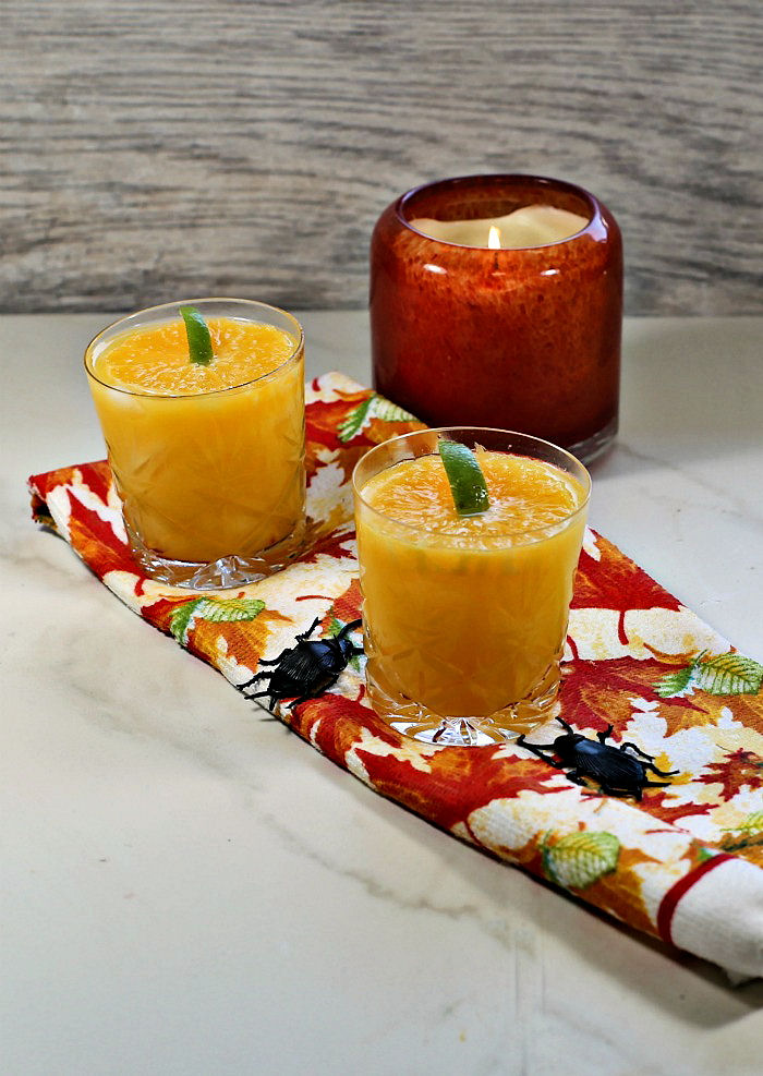 Pumpkin top garnishes made with orange slices ono a fall towel with an orange candle.