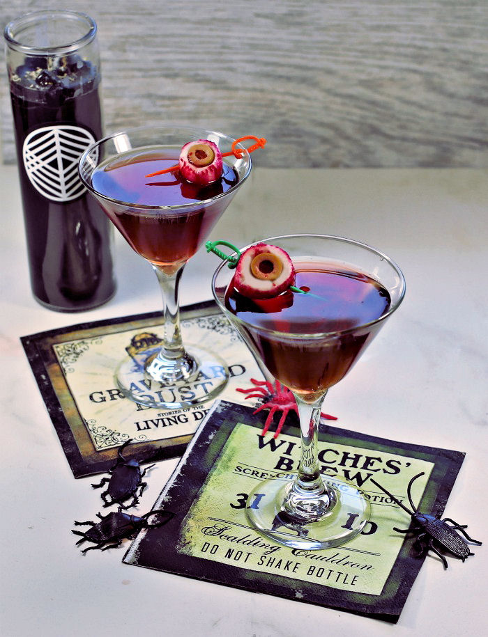 Halloween cocktail garnishes - radish eyeballs on skewers in a red drink with Halloween napkins and candle.