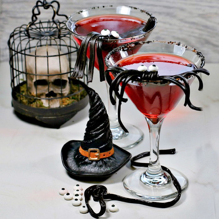 Halloween cocktail garnishes - Licorice spider Halloween cocktail with skull and witches hat.