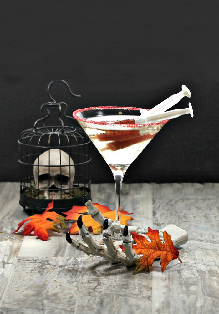 Halloween cocktail garnishes - blood filled syringes in champagne with a skeleton hand and skull.