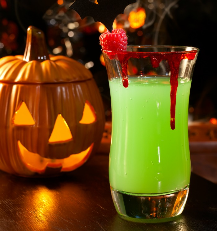 Halloween cocktail special effects - Bloody glass rim on a green drink with a pumpkin.